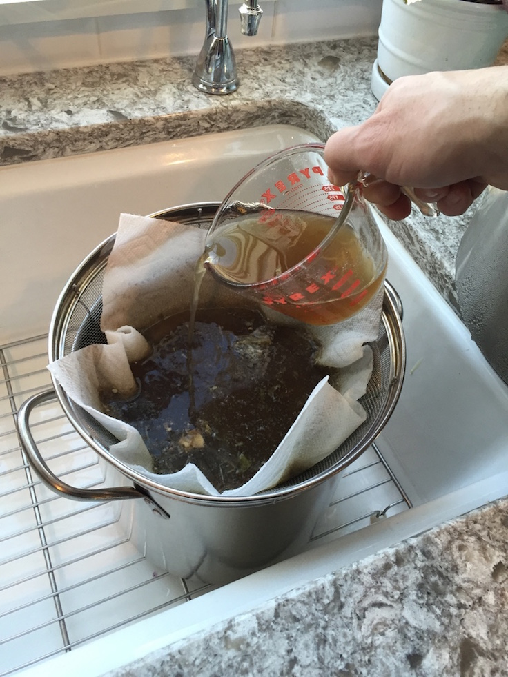 A large metal strainer with a medium stock pot and some cheese cloth or a paper towel makes it easy to filter your stock.